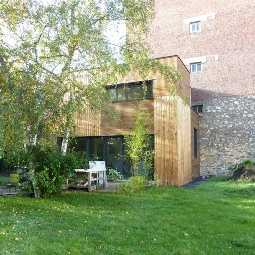 Photo couleur d'une maison en bois et son jardin construite par le cabinet TB'Home