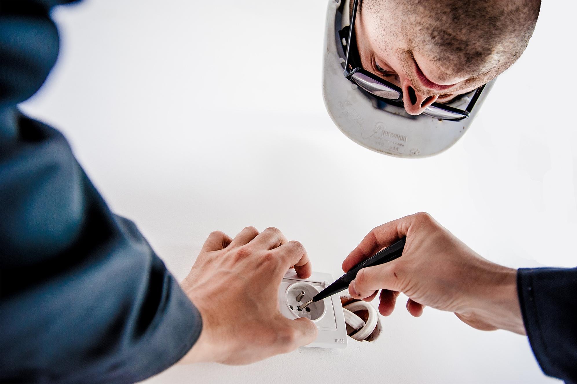 Photo couleur illsustrative d'un homme en train de faire des travaux d'électricité pour illustrer la préparation des travaux et maîtrise d'oeuvre par TB'Home Architecteurs
